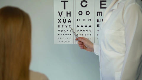 Eye doctor checking eyesight of female patient, reception at the ophthalmologist Footage