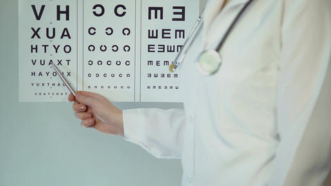 Female oculist pointing at table with small letters, checking patient's eyesight Footage