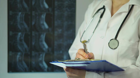 Surgeon analyzing patient's X-ray and writing down diagnosis in medical records Footage