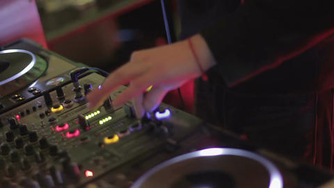 DJ playing music at mixing console, twisting controls on sound board, nightclub Footage