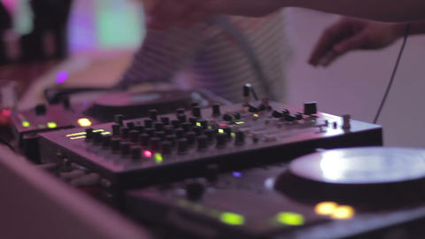 Hands of male dj turning controls on sound equipment, playing music in nightclub Footage