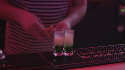 Active bartender making and serving alcohol shots to nightclub party guests Footage