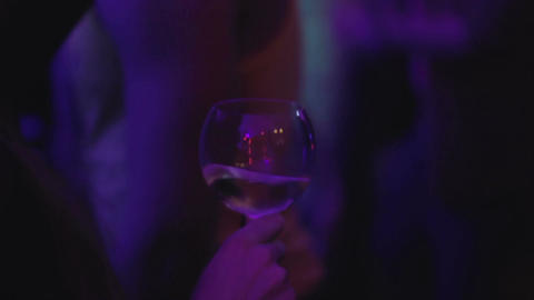 Beautiful young woman moving to music on dance floor with glass of wine, party Footage