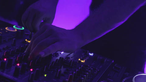Closeup shot of male dj hands turning controls on sound equipment at club party Footage