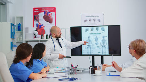 Experienced man doctor analysing human skeleton image with colleagues Live Action