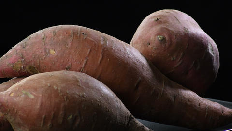 Sweet potatoes gyrating on a black tray with black background. Ipomoea Batatas Live Action