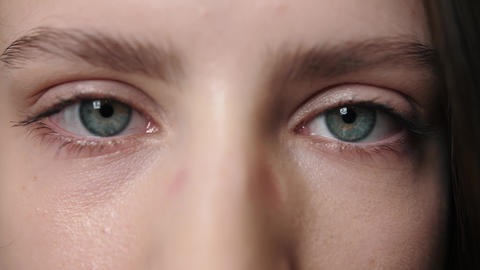 Woman open blue eyes. Close up of female face with wide blue eyes. Brunette Live Action
