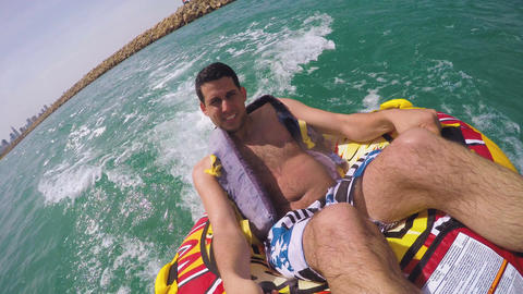 Man sitting in inflatable ring towed by a boat in the water and recording himsel Footage