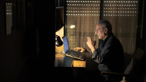 hidden views of old man while smoking and typing on his computer Footage