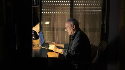 Old man smoking, while chatting with his computer Footage