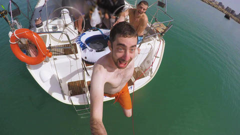 Young man filming himself thrown into the water from a boat by his friends Live Action