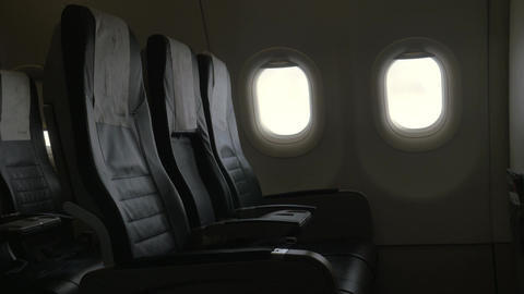 Seen interior decor of plane - black leather chairs and two portholes Footage