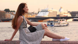 Slim woman sit against river and parked cruise liner, summer evening GIF