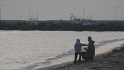 In Nea Kallikratia, Greece on sea coast a young mother with a small son throwing Footage