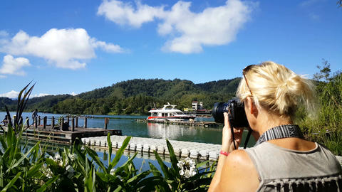 European blonde photographer takes pictures of lake Footage