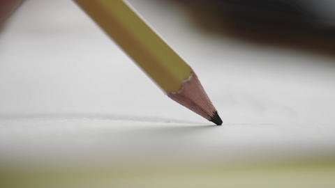 A close-up of a slate pencil draws on a white sheet of paper. Drawing or sketching Live Action