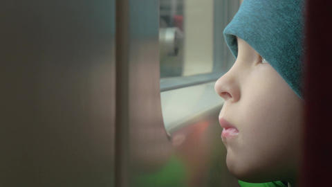 Sad child looking out the window of train Footage