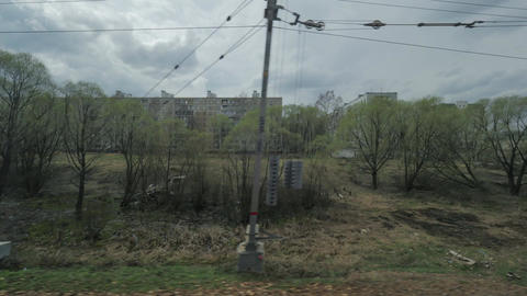 View from the window of a moving train seen trees, buildings, bridges and railro Footage