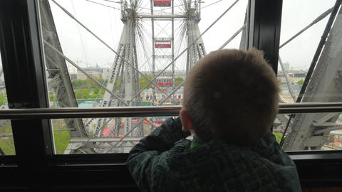In Vienna, Austria from the window booths of the ferris wheel little boy looks a Footage