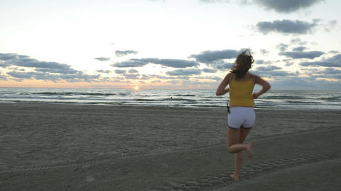 Girl running on the beach at sunrise Footage