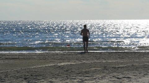 Man running towards the sea on the beach Footage