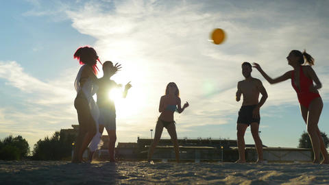 Group of friends enjoying their time at the beach and playing volleyball Footage