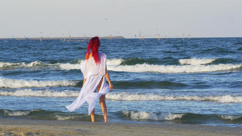Redhead Caucasian young woman walking along the sea and playing with her feet in Footage