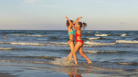 Females playing on the beach in the water and dancing Live Action