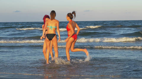Three beautiful girlfriends teasing one another and playing in the sea Footage