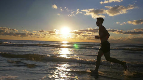 Runner doing workout on a beautiful beach at sunrise in slow motion Footage