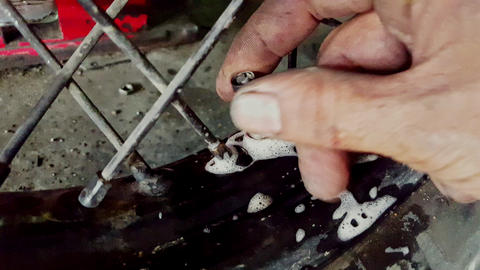 Closeup Man Fingers Bind Nipple on Tire Disk in Shop Live Action