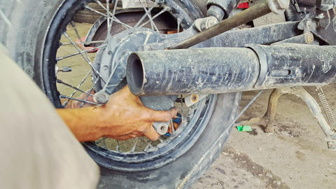 Closeup Man Assembles Wheel to Motorcycle in Repair-shop Footage