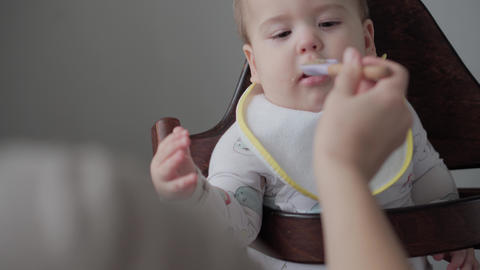 first feeding, food, nutrition, childhood concepts - Mom feeds infant baby with Live Action
