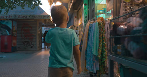 Little boy walking down the street with shops Footage
