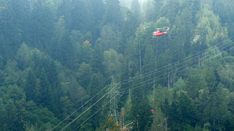 helicopter transporting cement to construction site in alps Live Action