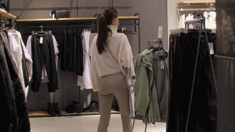 Professional image designer with ponytail walks along shop Live Action