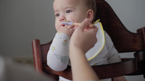 food, nutrition, childhood concepts - medium shot Mom feeds infant baby with Live Action