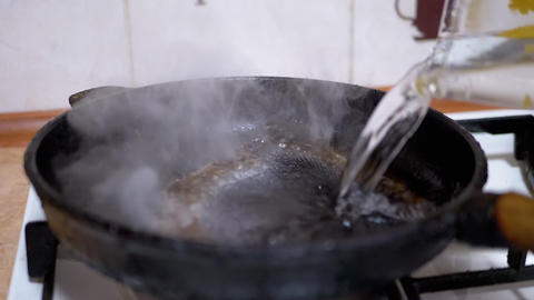 Pouring Water from Glass in Hot, Greasy Skillet. Boiling Liquid, Evaporation Live Action