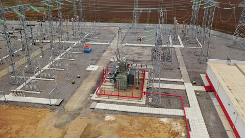 Transformer at the power station with metal towers and power lines around it, 4k Live Action
