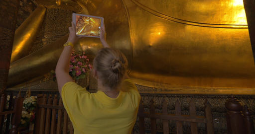 Tourist with pad taking photo of reclining Buddha statue in Bangkok Footage