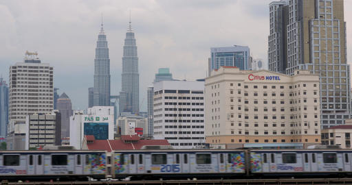 By rail passes train. In the background seen Petronas Twin Towers, hotel and sky Footage