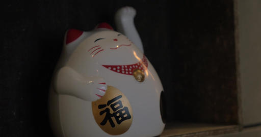 Fortune cat figurine beckoning with paw