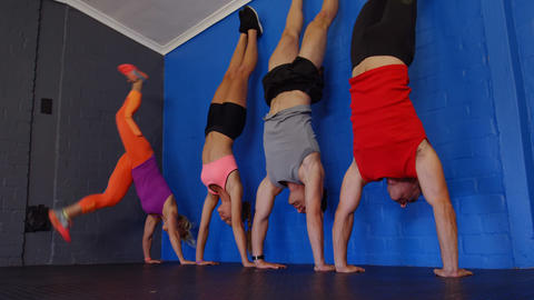 Fitness trainer assisting people to perform handstand Live Action