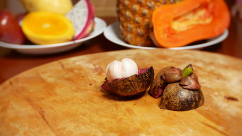 exotic fruits on the table. 4k. Mangostin rotates on the cutting board Live Action