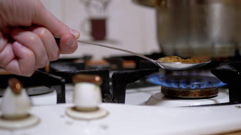 Hand Male Addict Cooks Heroin in Spoon Over Gas Stove at Home Live Action