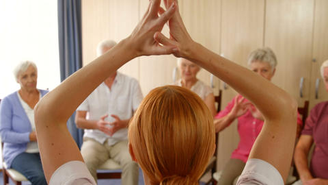 Therapist assisting group of senior people with exercise Footage