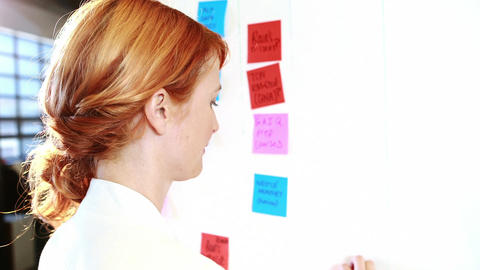 Woman putting sticky notes on whiteboard Live Action