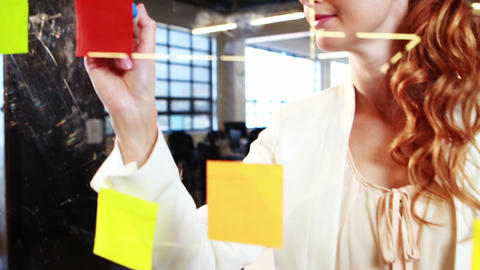 Woman writing on sticky notes Live Action