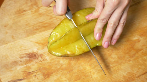 exotic fruits on the table. 4k, Female hands cut a carambola with a knife on a Live Action