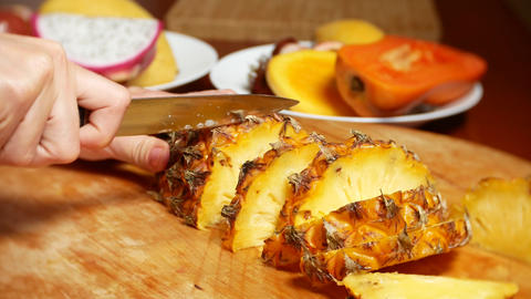 exotic fruits on the table. 4k, female hands cut pineapple with a knife on a Live Action